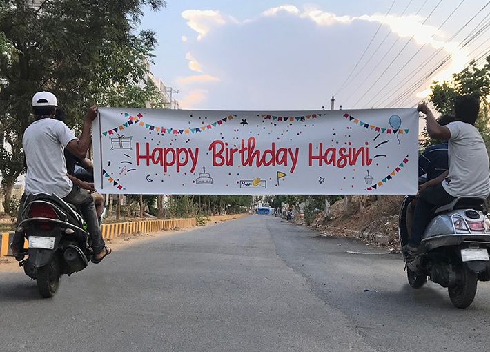 Boys holding birthday wishing banner on road riding bikes